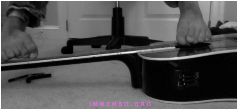 ragazzo che suona chitarra con piedi
